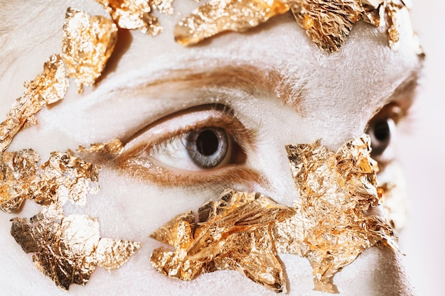 A girl with an unusual make-up with white skin and blue eyes. long eyelashes. golden mask. gold leaf.