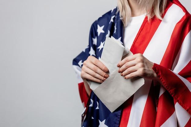 Девушка с флагом сша держит конверт с голосованием