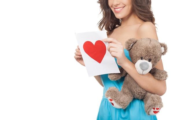 발렌타인 데이 카드와 함께 소녀입니다. 흰색 배경에 격리된 채 발렌타인 데이 카드를 읽는 아름다운 젊은 여성의 이미지