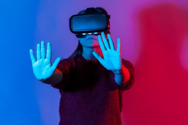 Девушка в очках виртуальной реальности на голове играет в симулятор игры, стоя с протянутыми руками