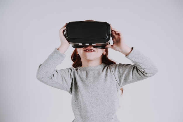 Girl with virtual reality glasses plays game.
