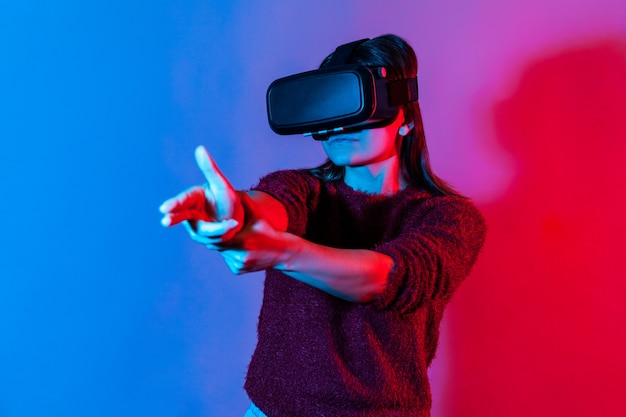 Girl with vr glasses on head playing shooter game, pointing finger gun and shooting right on target