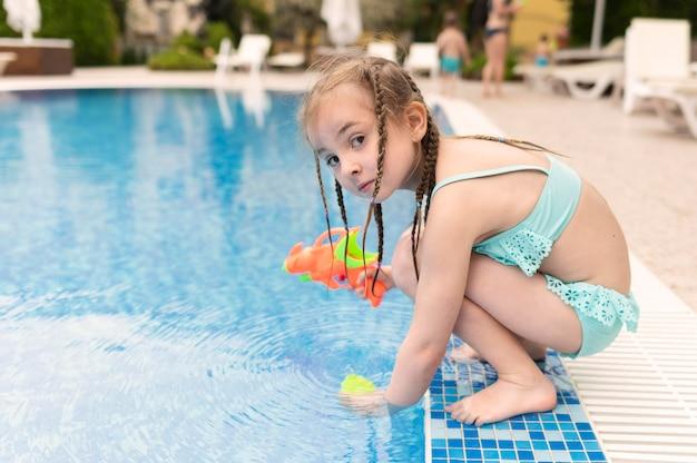 수영장에서 물 총을 가진 소녀