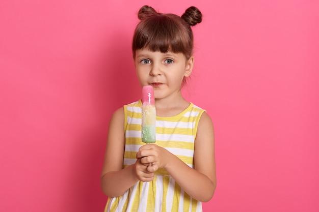 カメラを直接見て、バラ色の背景の上に孤立したポーズのウォーターアイスクリームを持つ少女は、面白い結び目で立っている白と黄色の縞模様の服を着て、カメラを見てください。