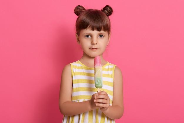 ピンクの背景に分離されたポーズのウォーターアイスクリームを持つ少女、白と黄色の縞模様の夏のドレスを着て、面白い結び目で立っています。