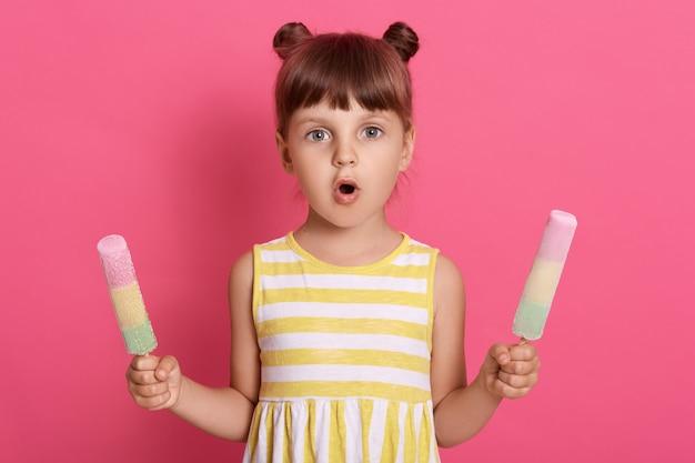 Ragazza con gelati d'acqua in entrambe le mani che indossa un abito a righe, con due nodi, in posa con l'espressione del viso stupita contro il muro rosa.
