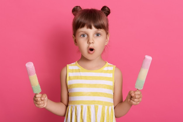 ピンクの壁にびっくりした表情でポーズをとって、2つの結び目がある縞模様のドレスを着て両手でウォーターアイスクリームを持つ少女。