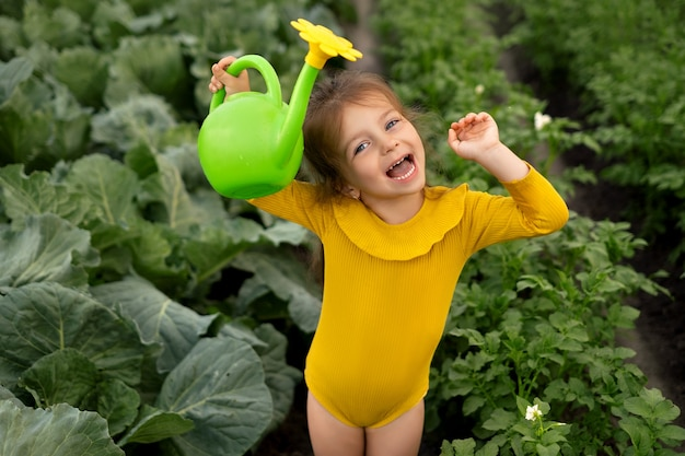 A girl with a watering can in her hands is watering a vegetable garden with cabbage