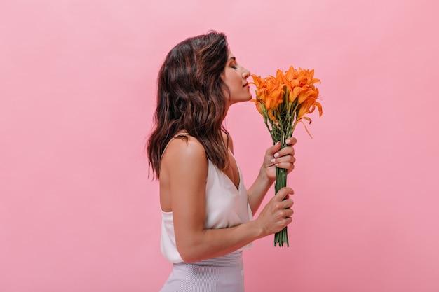 La ragazza con i capelli mossi gode del profumo dei bellissimi fiori d'arancio. la donna dai capelli scuri in abito alla moda leggero annusa un grande bouquet.