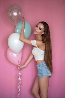 ピンクの背景に、ヘリウム気球を手に持って楽しんでいるウェーブのかかった髪の少女。