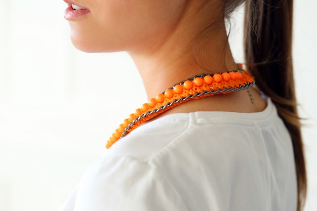 Girl with wearing orange necklace