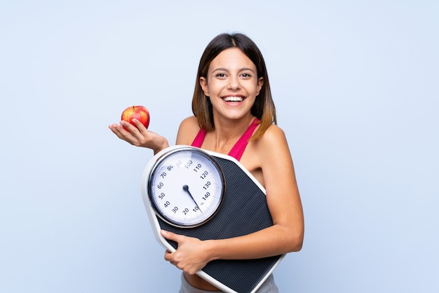 Girl with weighing machine over isolated blue  with weighing machine and with an apple