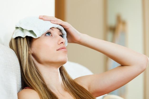 Девушка с мокрым полотенцем на лбу