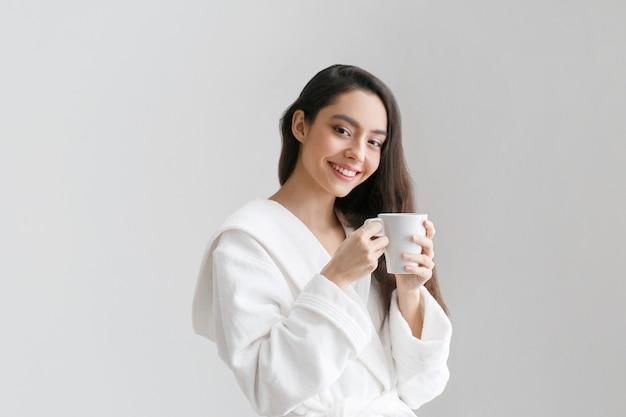 手に白いカップを持つ少女。ドリンクティーやコーヒーの女性のindors家とカジュアルな女性の肖像画。スタジオショット。