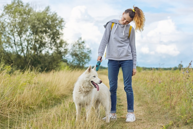 Girl with white dog, teenager walking with husky pet