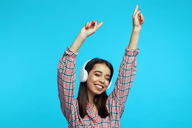 Девушка в белых наушниках слушает музыку и танцует с поднятыми руками
