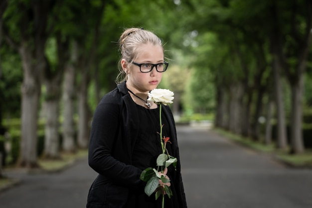 Girl with white rose mourning deceased on graveyard