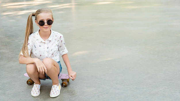 Girl with white shirt sitting on skateboard