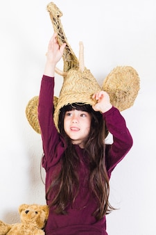 Girl with wicker elephant mask on her head