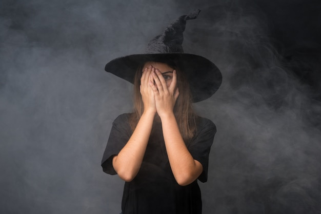 Girl with witch costume for halloween parties over isolated dark wall covering eyes and looking through fingers
