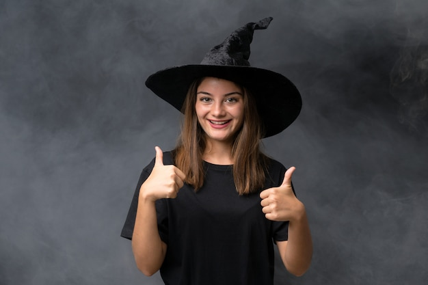 Girl with witch costume for halloween parties over isolated dark wall giving a thumbs up gesture