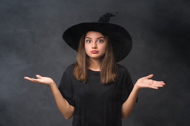Girl with witch costume for halloween parties over isolated dark wall having doubts with confuse face expression