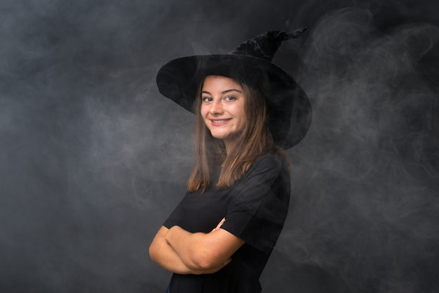 Girl with witch costume for halloween parties over isolated dark wall laughing