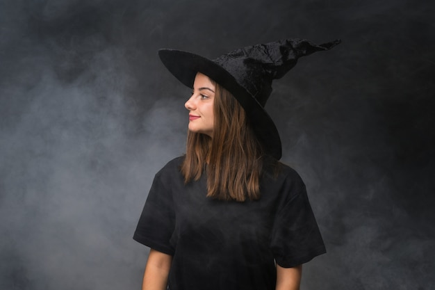 Girl with witch costume for halloween parties over isolated dark wall looking to the side