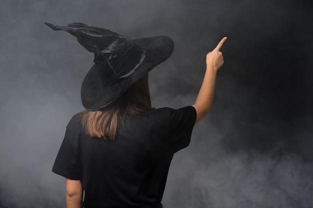 Girl with witch costume for halloween parties over isolated dark wall pointing back with the index finger
