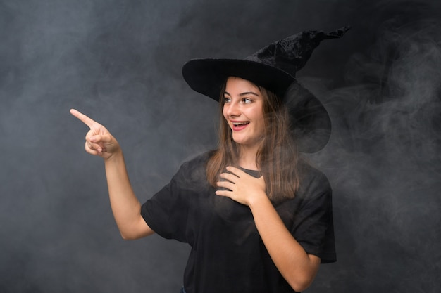 Girl with witch costume for halloween parties over isolated dark wall pointing finger to the side