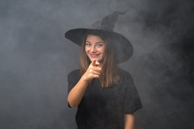 Girl with witch costume for halloween parties over isolated dark wall points finger at you
