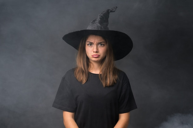 Girl with witch costume for halloween parties over isolated dark wall sad