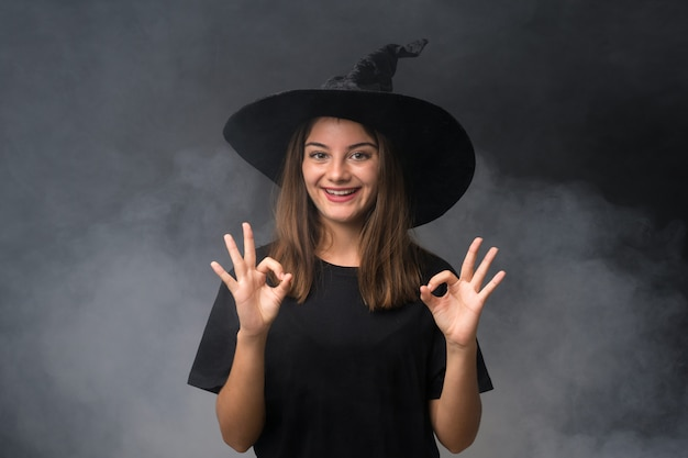 Girl with witch costume for halloween parties over isolated dark wall showing an ok sign with fingers