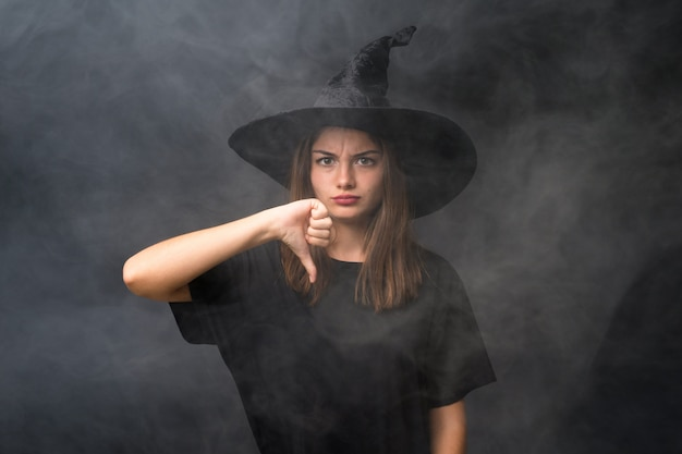 Girl with witch costume for halloween parties over isolated dark wall showing thumb down sign