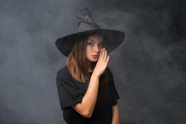 Girl with witch costume for halloween parties over isolated dark wall whispering something