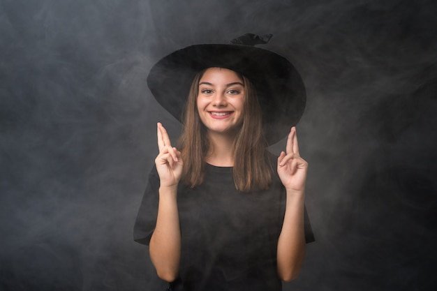 Girl with witch costume for halloween parties over isolated dark wall with fingers crossing