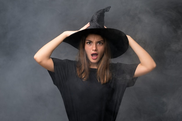 Girl with witch costume for halloween parties over isolated dark wall with surprise facial expression