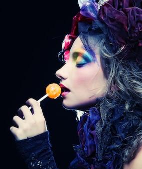 Девушка с творческим макияжем держит леденец на палочке. кукольный стиль.