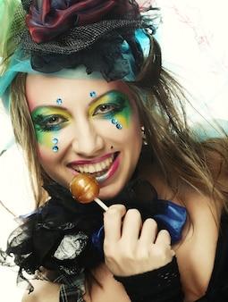 創造的なメイクで女の子はロリポップを保持しています。人形のスタイル。
