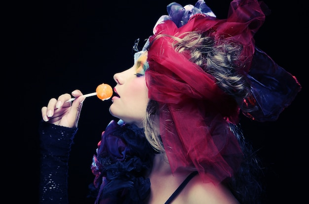 Girl with  with creative make-up holds  lollipop
