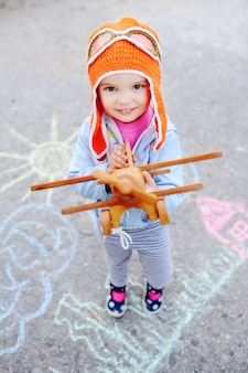 Girl with wooden toy airplane and orange pilot cap