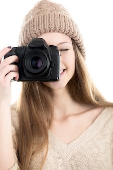 写真を撮るウールキャップを持つ少女