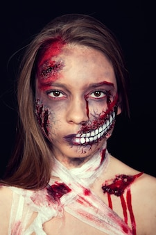 Girl with wounds on her face, bloody stains, makeup for halloween, girl