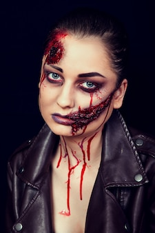 Girl with wounds on her face, bloody stains, makeup for halloween