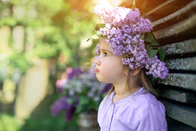 A girl with a wreath of lilac on her head looks away, pursing her lip.