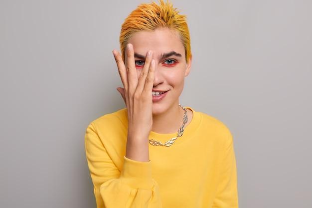 Ragazza con acconciatura gialla trucco luminoso guarda attraverso le dita sorride misteriosamente indossa piacevolmente maglione casual e catena di metallo su grigio