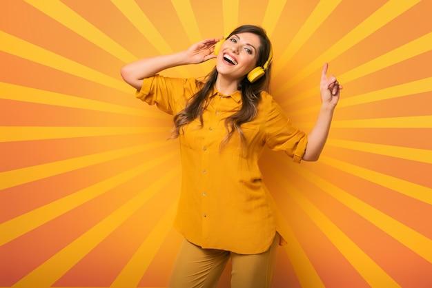 노란색 헤드셋을 가진 소녀는 음악을 듣고 정서적이고 활기찬 표현을 춤을 춥니 다.