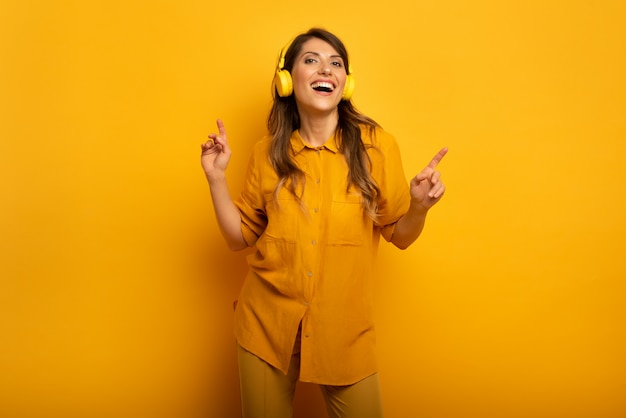 노란색 헤드셋과 소녀는 음악과 춤을 수신합니다. 정서적이고 활기찬 표현