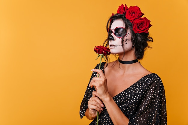 Girl with zombie mask for halloween smells fragrant rose. model in black dress on orange wall