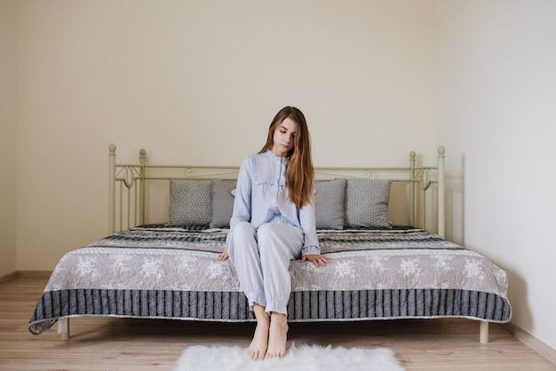 The girl woke up and sits in her pajamas on the bed in her room. stylish gray-white interior.